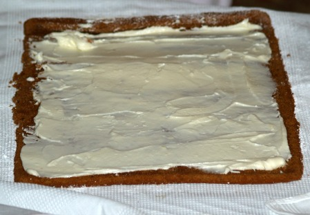 spreading filling on unrolled pumpkin cake