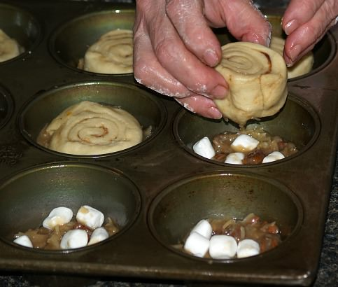 Place Bun for Coconut Glazed Sticky Buns on Top of Frosting and Marshmallows