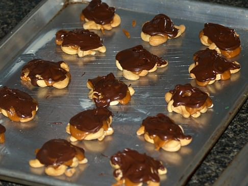 Melted Chocolate Spooned Over Cashews and Cream Mixture